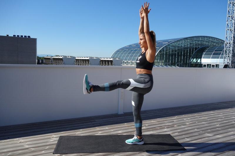 девушка делает упражнение воин с подъемом ноги
