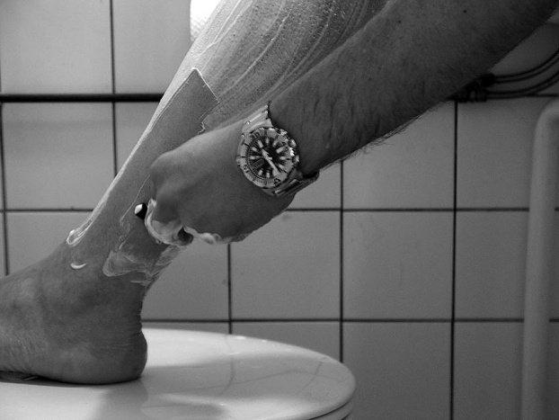 мужчина бреет ноги станком