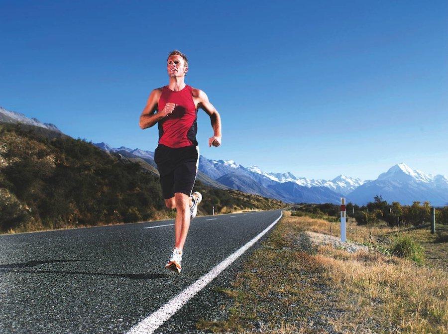 парень бежит по асфальтной дороге на фоне гор